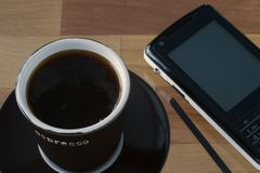 Coffee cup and mobile phone. Brown espresso mug. Black mobile phone. On wooden table top Stock Image