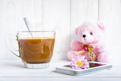 Coffee cup and a mobile phone with flowers on the white wooden. Stock Photos