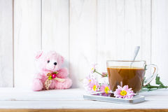 Coffee cup and a mobile phone with flowers on the white wooden. Royalty Free Stock Photo
