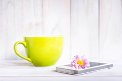 Coffee cup and a mobile phone with flowers on the white wooden. Stock Image