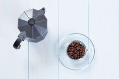 Coffee cup and moka pot with coffee beans on table. Coffee cup full of coffee beans and moka pot on a wood table Royalty Free Stock Photos
