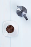 Coffee cup and moka pot with coffee beans on table Royalty Free Stock Photography