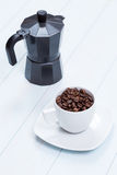 Coffee cup and moka pot with coffee beans on table Stock Photos