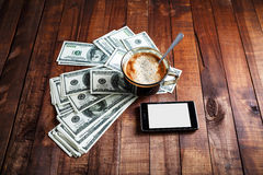 Coffee cup, money and phone. Coffee cup, money, dollars and phone on vintage wooden table background. Business concept Stock Image