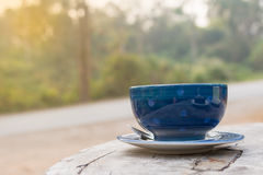 Coffee Cup. Morning coffee cup on wooden table, The roadway with yellow light background Stock Images