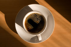 Coffee cup in the morning sun. On the office table stock photo