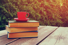 Coffee cup mug and book over wooden table outdoors, at afternoon time. selective focus Stock Photo