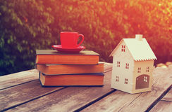 Coffee cup mug and book over wooden table outdoors, at afternoon time. small house model over wooden table outdoors at garden Stock Photos