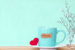 Coffee cup mug with red heart shapeand happy word tag on wooden Royalty Free Stock Photo