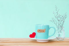 Coffee cup mug with red heart shapeand happy word tag on wooden Stock Photo