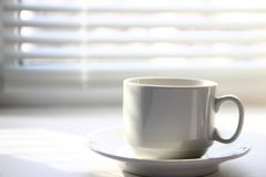 Coffee cup near window. Coffee cup near the window on the background of blinds and shadows royalty free stock photos