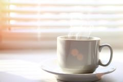 Coffee cup near window. Coffee cup near the window on the background of blinds and shadows royalty free stock photo