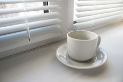 Coffee cup near window. Coffee cup near the window on the background of blinds and shadows stock photo