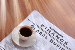 Coffee cup on a newspaper Stock Images