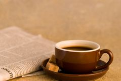 Coffee cup and newspaper. Coffee in brown cup with sugar lumps next next to newspaper, plain background with copy space Stock Images