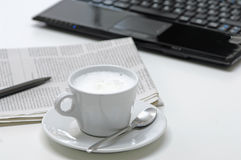 Coffee cup with newspaper and laptop in background Stock Photos