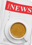 Coffee cup on newspaper Stock Photos