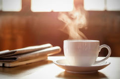 Coffee cup with newspaper on the table, coffee shop background,. Warm tone stock photo