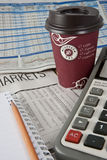 A coffee cup on Newspapers. Newspapers, coffee cup, Note book, pencil and calculator stock image
