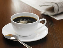 Coffee cup and newspapers Stock Photos