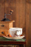 Coffee cup with Nostalgic coffee grinder on background Royalty Free Stock Photography