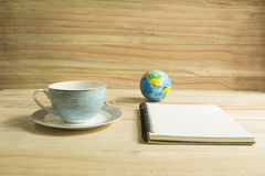 Coffee cup and note book on  wooden table. Stock Images