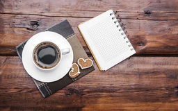 Coffee cup and note book on wooden tabletop. Black coffee with cookies and note book on table Stock Photo