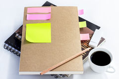 Coffee cup with notebook and  blank yellow paper note on white t Royalty Free Stock Photo
