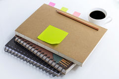 Coffee cup with notebook and blank yellow paper note on white ta Stock Images