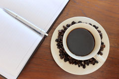 Coffee cup with notebook Stock Image