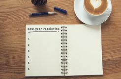 Coffee cup and notebook with new years resolution on rustic desk. From above, planner and checklist concept stock images