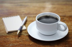 Coffee cup notebook and pen on the wooden table Stock Image