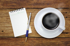 Coffee cup notebook and pen on the wooden table  Royalty Free Stock Photos