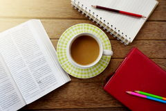 coffee cup,notebook,pencils on dark wooden table Stock Image