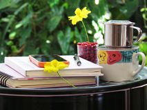 Coffee cup, notebooks, pencil and flowers on green steel table do it yourself. corner relax concept. Stock Photo