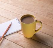 Coffee cup with notebooks and pencils. Royalty Free Stock Image