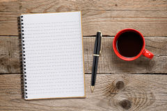 Coffee cup and notepad with pen Stock Image
