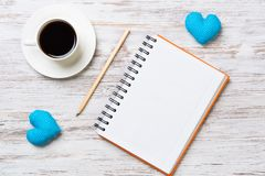 Confession on Valentines day. Coffee cup notepad pencil and two hearts on wooden surface Royalty Free Stock Photo