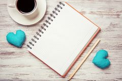 Confession on Valentines day. Coffee cup notepad pencil and two hearts on wooden surface Stock Images