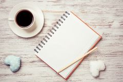 Confession on Valentines day. Coffee cup notepad pencil and two hearts on wooden surface Stock Photos