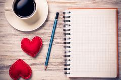Confession on Valentines day. Coffee cup notepad pencil and two red hearts on wooden surface Stock Image