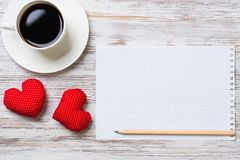 Confession on Valentines day. Coffee cup notepad pencil and two red hearts on wooden surface Stock Photography