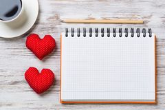 Confession on Valentines day. Coffee cup notepad pencil and two red hearts on wooden surface Stock Photos
