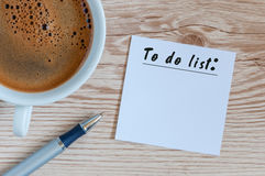 Coffee cup and notice with to do list on wooden rustic table from above, planning, design concept Stock Photography