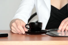 Coffee cup at office. On a table on a background of the girl in a white shirt Royalty Free Stock Photography
