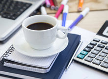 Coffee Cup at Office with Financial Papers,Agenda and Calculator Stock Photo