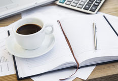 Coffee Cup at Office with Financial Papers,Agenda and Calculator Stock Image