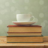 Coffee cup on old books. Over blur background Royalty Free Stock Photos