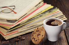 Coffee cup and old magazines Stock Photo