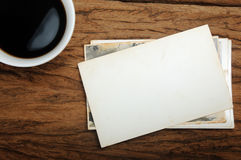 Coffee cup and old paper photo frame on wood background Stock Photos